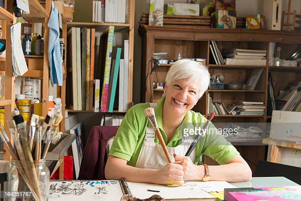 Senior woman artist with two brushes art studio