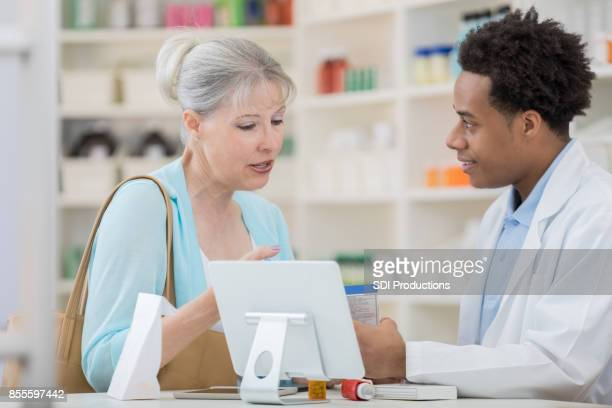 senior woman asks pharmacy technician about cold medication - technician stock pictures, royalty-free photos & images