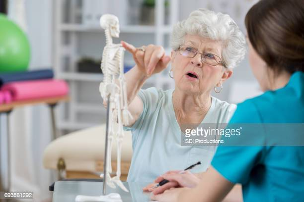 Senior woman asks physical therapist question about injured shoulder