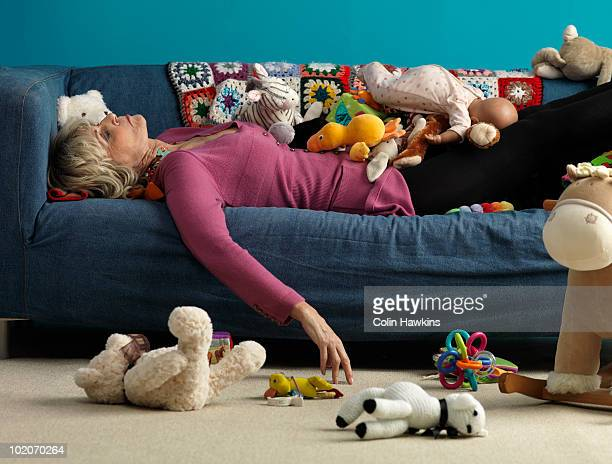Senior woman asleep on sofa with toys