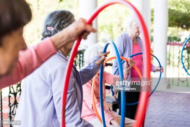 Senior vrouw aan een fitness-klasse buiten zitten in een rij