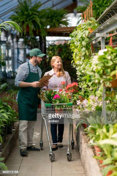 Senior woman at a garden center purchasing plants and salesman helping her