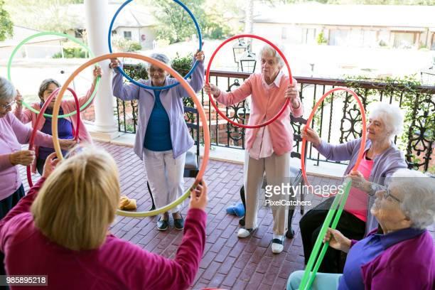 Senior vrouw op een groep fitness klasse buitenshuis