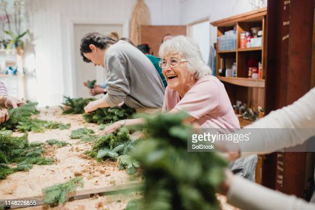 senior woman at a wreath-making workshop - old lady funny stock pictures, royalty-free photos & images