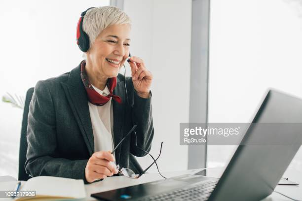 senior woman at call center - hands free device stock pictures, royalty-free photos & images