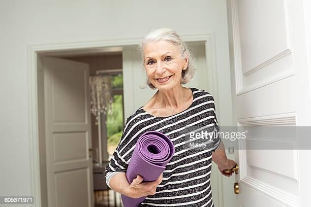 Senior woman at front door carrying yoga mat