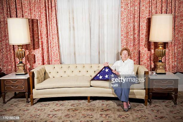 senior woman at home holding folded american flag - folded flag stock pictures, royalty-free photos & images