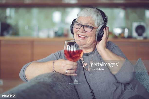 Senior woman at home listening music
