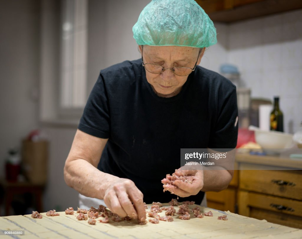 Senior woman at home making traditional food with dough and meat : Stock Photo