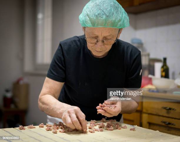 senior woman at home making traditional food with dough and meat - image technique stock pictures, royalty-free photos & images