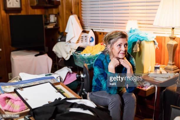 Senior mujer en casa, desordenada habitación