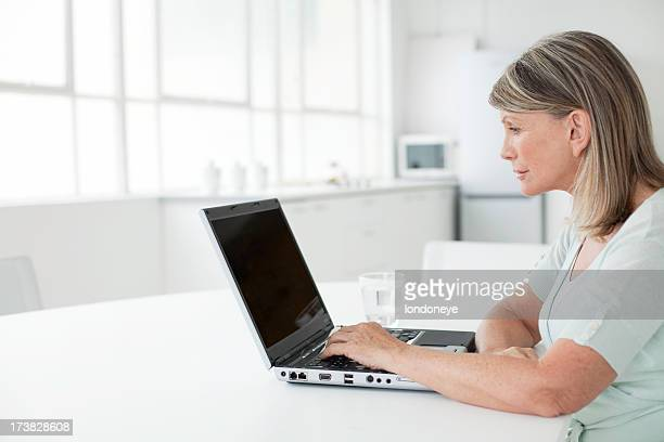senior woman at home on a laptop - overexposed stock photos and pictures