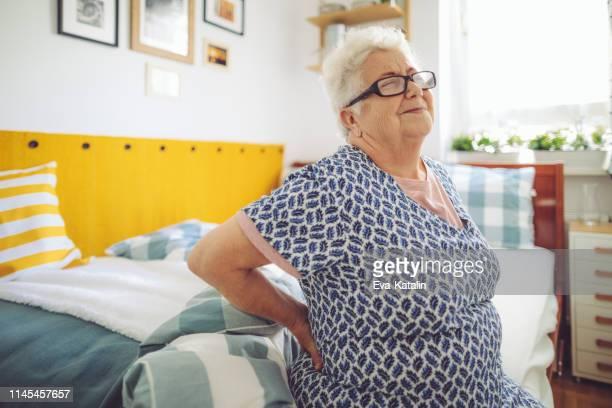自宅の先輩女性 - 下背部痛 ストックフォトと画像