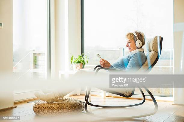 Senior woman at home with headphones and digital tablet