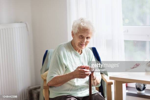 senior woman at home with walking cane