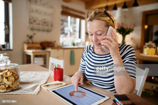Senior woman at home working on tablet, making phone call
