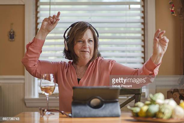 Senior woman at kitchen table listening and dancing to headphones