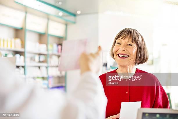 Ältere Frau im Apotheke Drogerie Check-out-Schalter