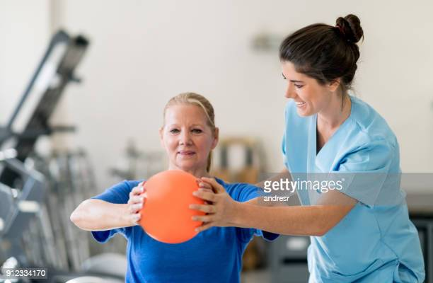 Senior woman at physical rehabilitation doing a chest workout and therapist helping her