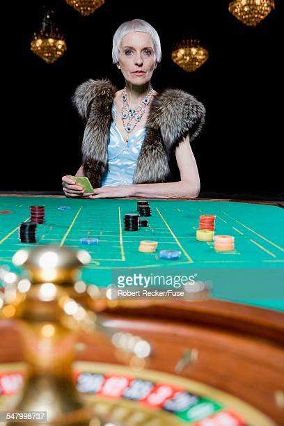 senior woman at roulette table - gambling table stock pictures, royalty-free photos & images