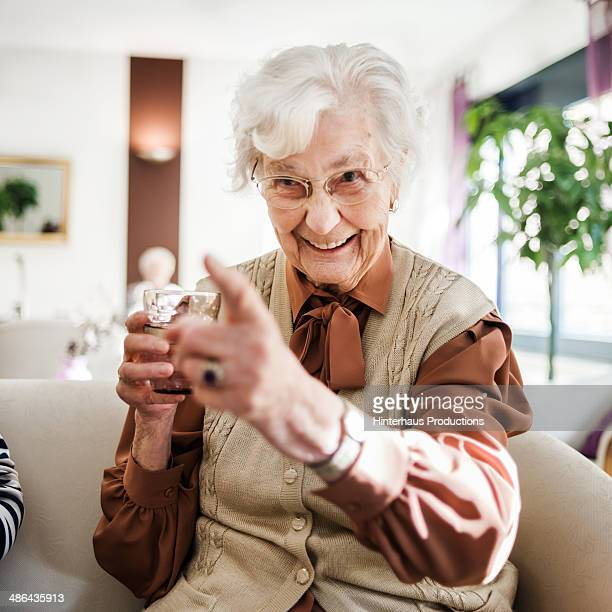 senior woman at sofa having fun - seniore vrouwen stockfoto's en -beelden