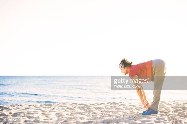 senior woman at the beach - older woman bending over stock pictures, royalty-free photos & images