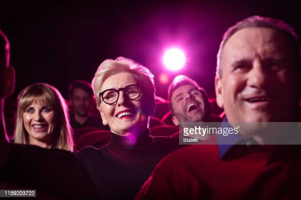 senior woman at theater watching movie - comedy film stock photos and pictures