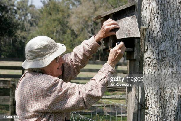 A senior woman attending a birdhouse at Dudley Farm Historic State Park