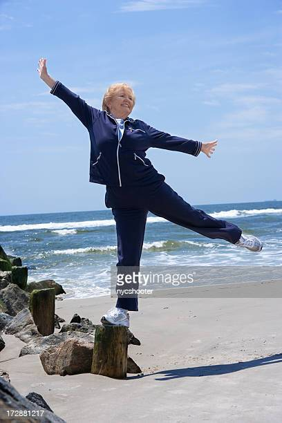 Senior woman balances on one leg
