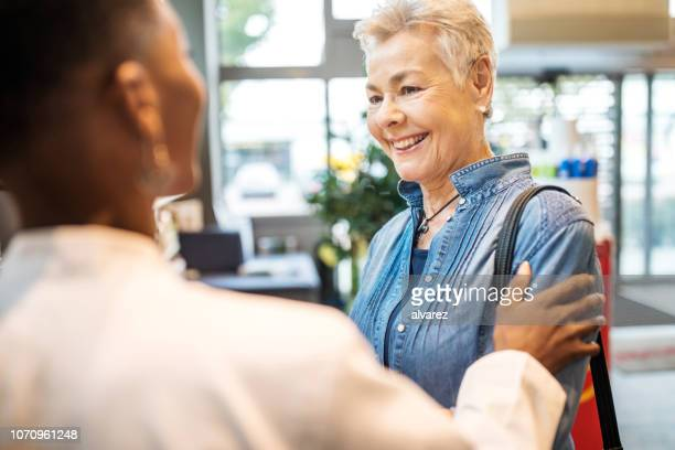 senior woman being assisted by pharmacist - hand on shoulder stock pictures, royalty-free photos & images