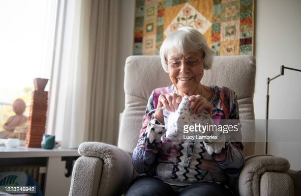 senior woman bending a piece of wire in a home made face mask, to fit her nose - medium shot stock pictures, royalty-free photos & images