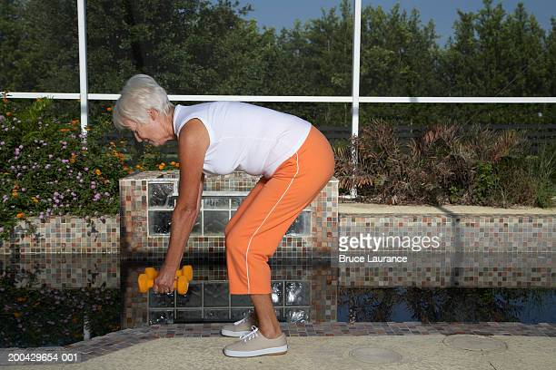 Senior woman bending over and lifting weights