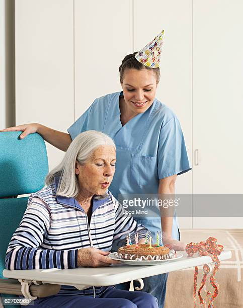 senior woman blow off the birthday candles - leaning disability stock pictures, royalty-free photos & images