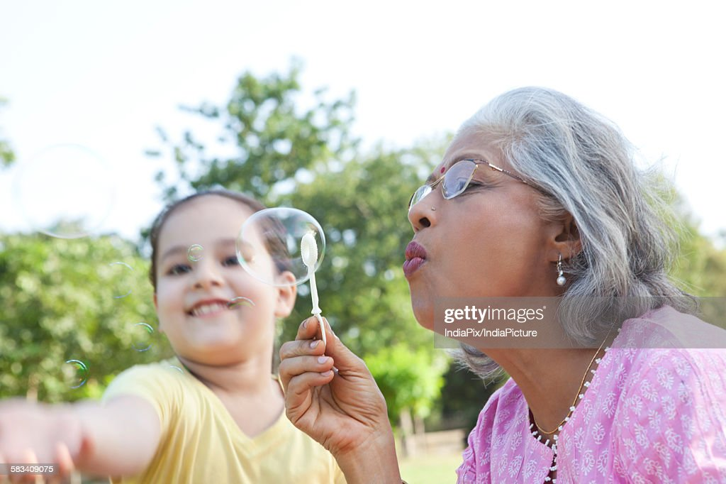 Senior woman blowing bubbles : Stock Photo