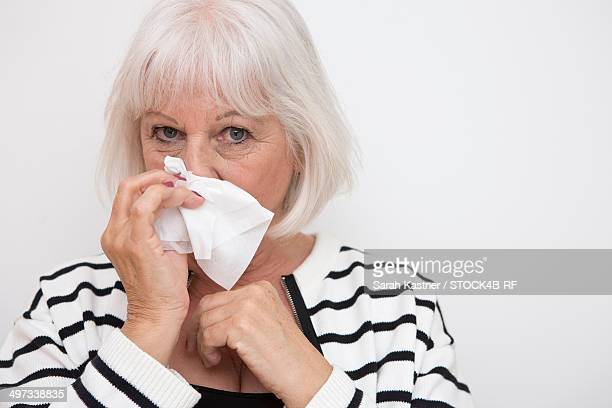 Senior woman blowing her nose, portrait