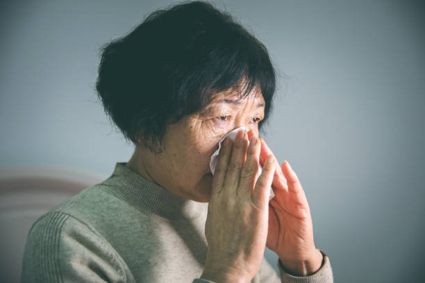 senior woman blowing nose - old asian woman crying stock pictures, royalty-free photos & images