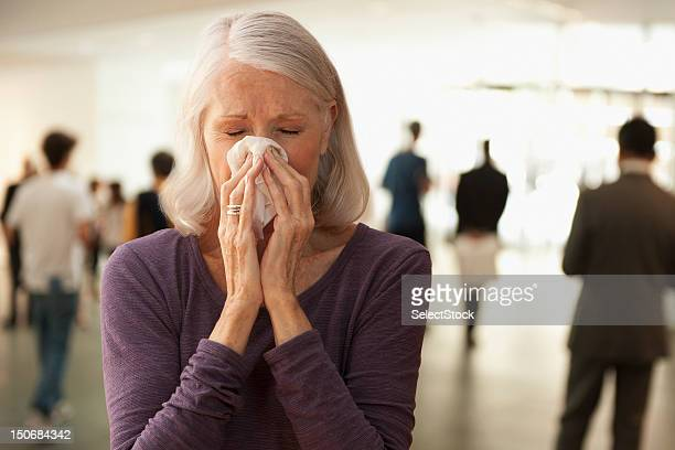 senior woman blowing nose - handkerchief stock photos and pictures