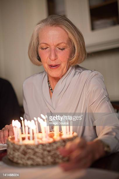 Senior woman blowing out candles on birthday cake