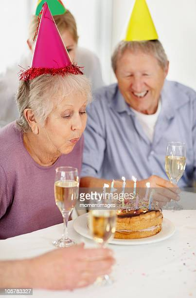Senior woman blowing out the candles on a birthday cake