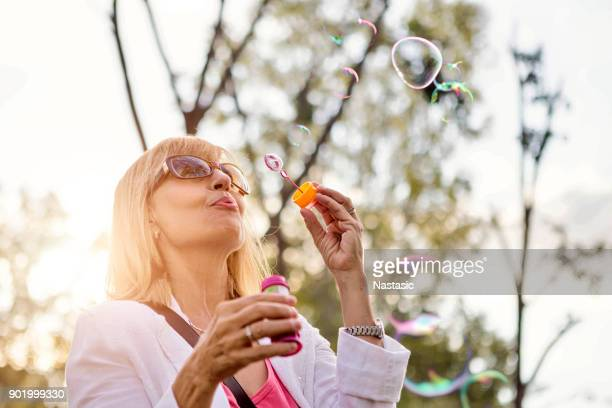 senior woman blowing soap bubbles - young at heart stock pictures, royalty-free photos & images