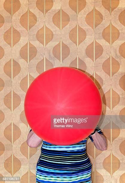 Senior woman blowing up a balloon
