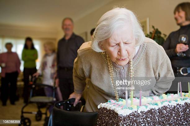 Senior woman blows out candles on birthday cake