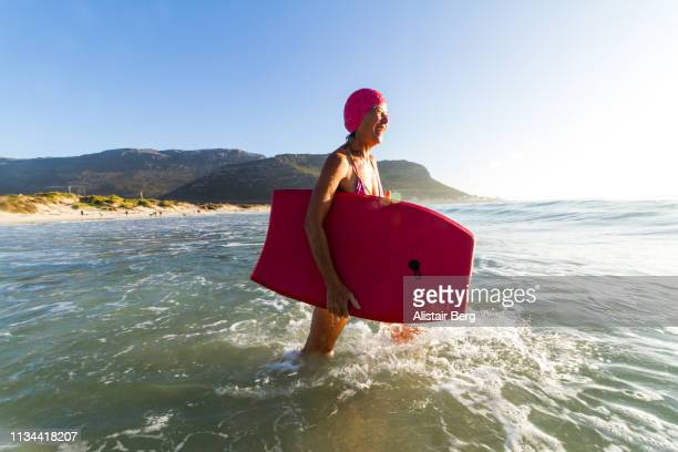 senior woman bodyboarding in the sea - independence stock pictures, royalty-free photos & images