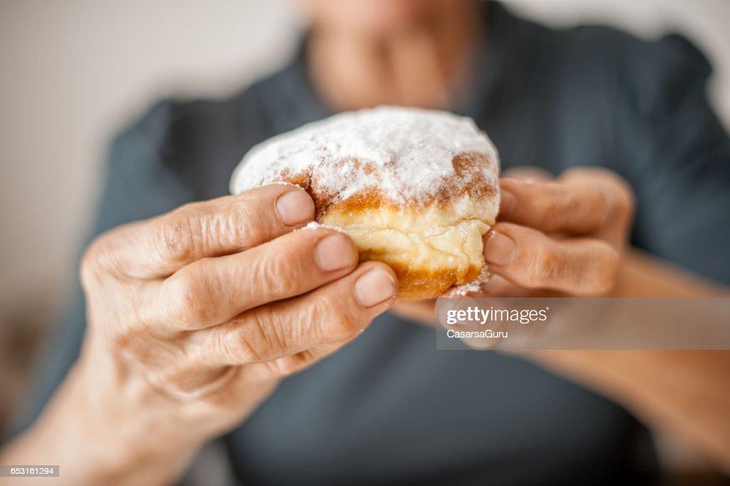 Femme Senior enfreindre les règles en mangeant des beignets : Photo