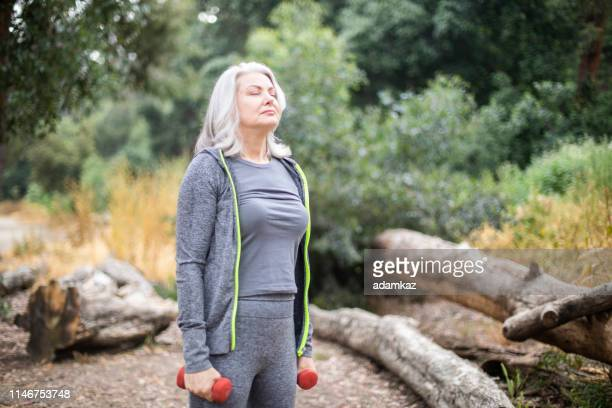 senior woman breathes calmly during workout - one senior woman only stock pictures, royalty-free photos & images