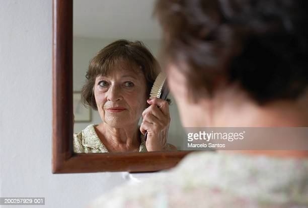 Senior woman brushing hair in mirror (focus on reflection)