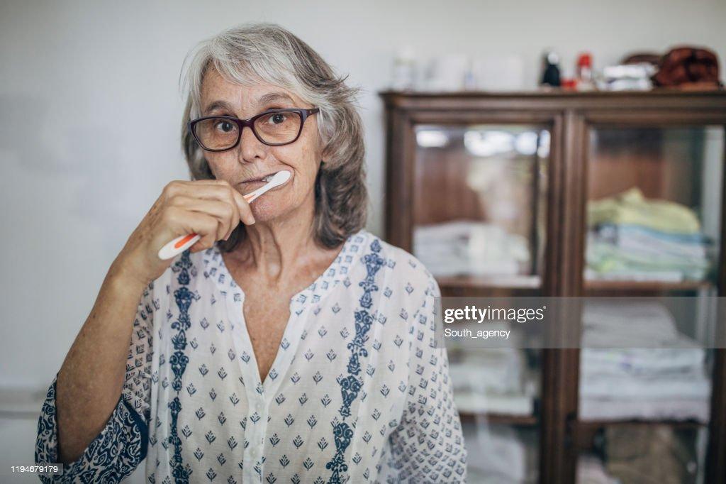 Senior Woman Brushing Teeth in Bathroom : Stock Photo