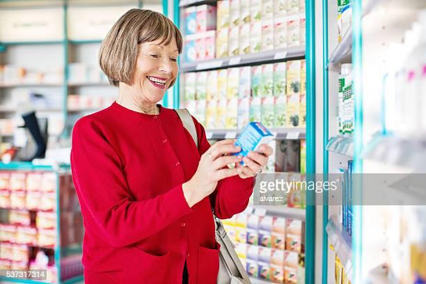 Senior woman buying medicine at pharmacy store