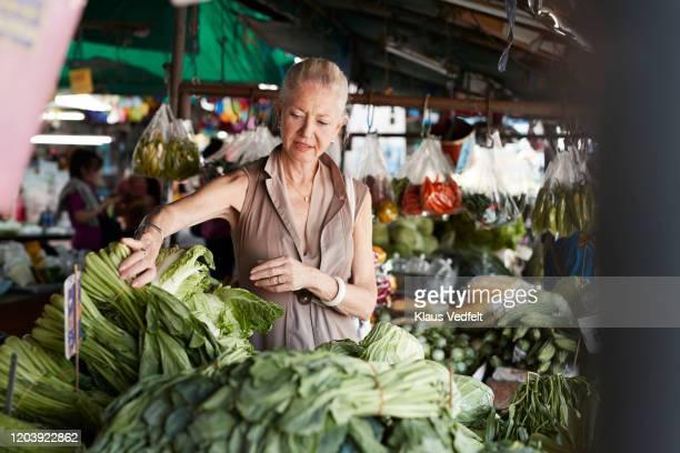 senior woman buying vegetable at market stall - 65 69 anni foto e immagini stock