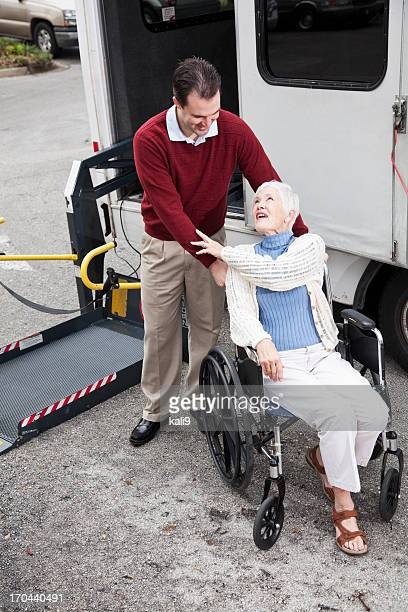 senior woman by minibus with wheelchair lift - disabled access stock photos and pictures